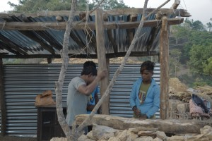 An emergency grant that got at least two months delayed: villagers setting up  a temporary shelter
