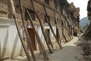 Kept erect only by heavy timber beams: damaged Khokana houses